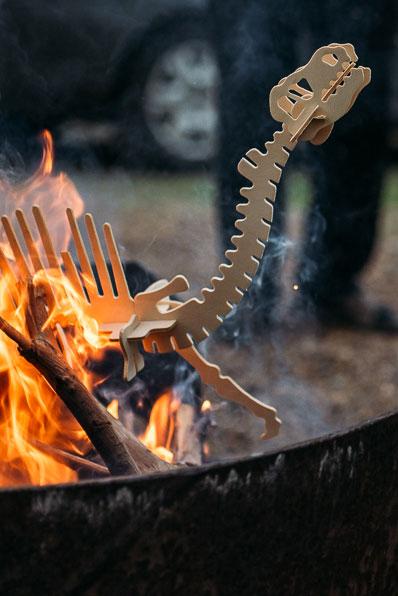 Wooden dinosaur burning in campfire