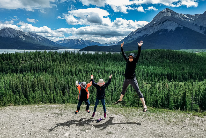 Mother and two children jumping in the air in the Rocky Mountains