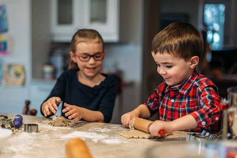 Boy and girl rolling cookie dough