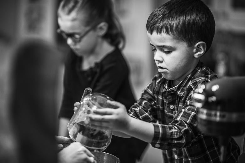 Boy emptying the contents of a measuring cup