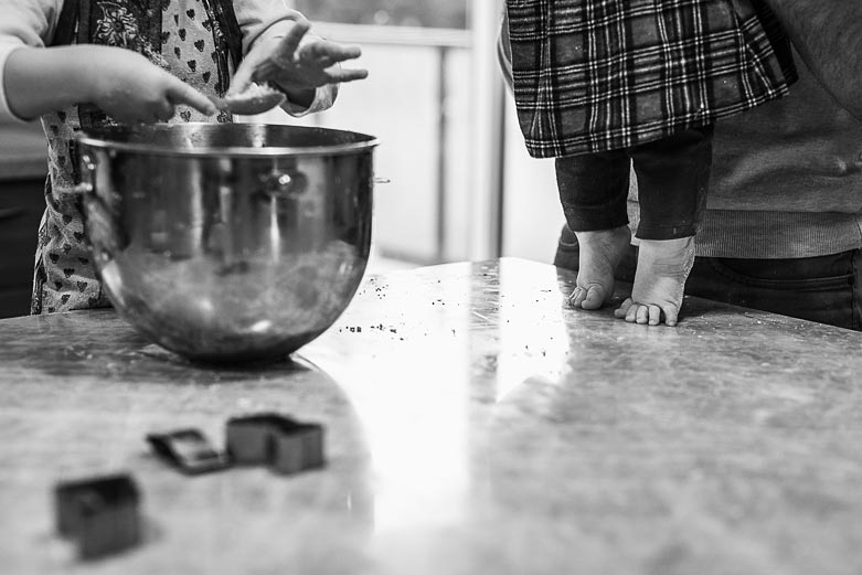 Baby feet on the counter next to a bowl of cookie dough