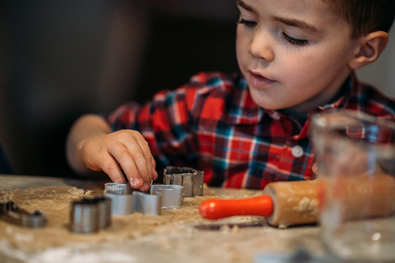 Boy cutting cookie dough with cookie cutter