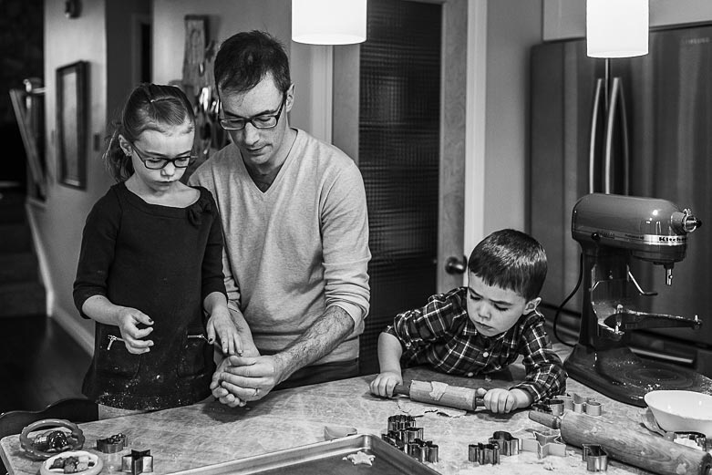 Father helping children with cookie making