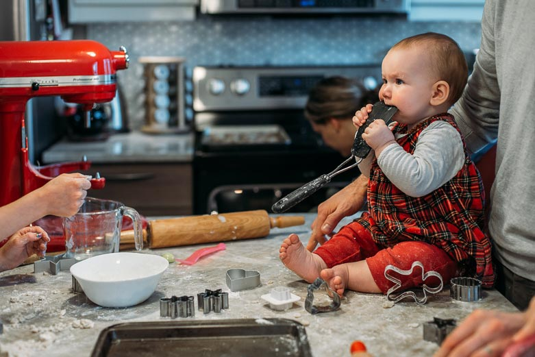 Baby on the kitchen counter with spatula in her mouth