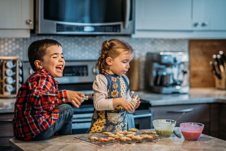 Boy laughing while decorating Christmas cookies with his sister