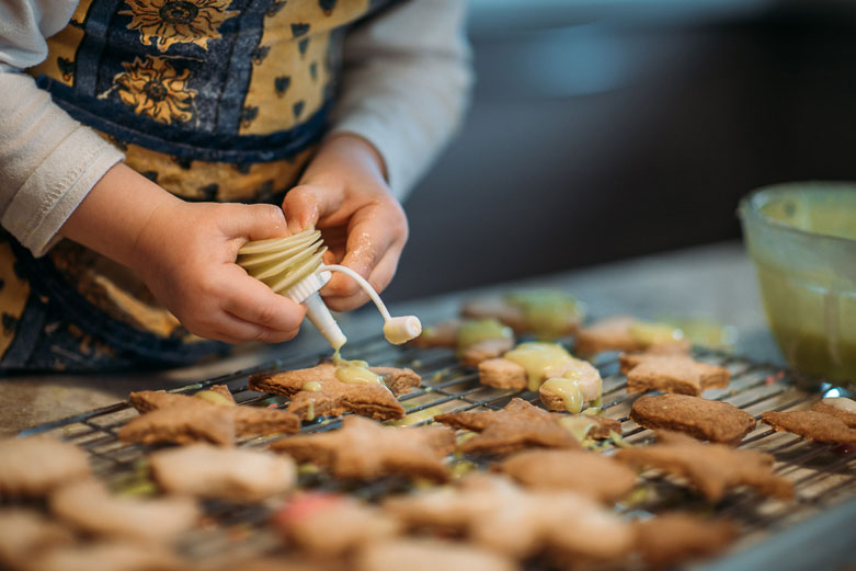 Girl's hands icing star-shaped Christmas cookies