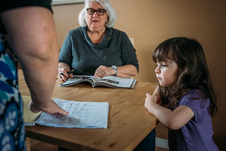 Girl and grandmother looking at mother's diaper log