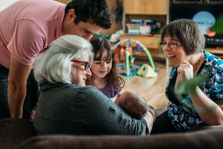 Parents, grandmother and sister looking at newborn baby