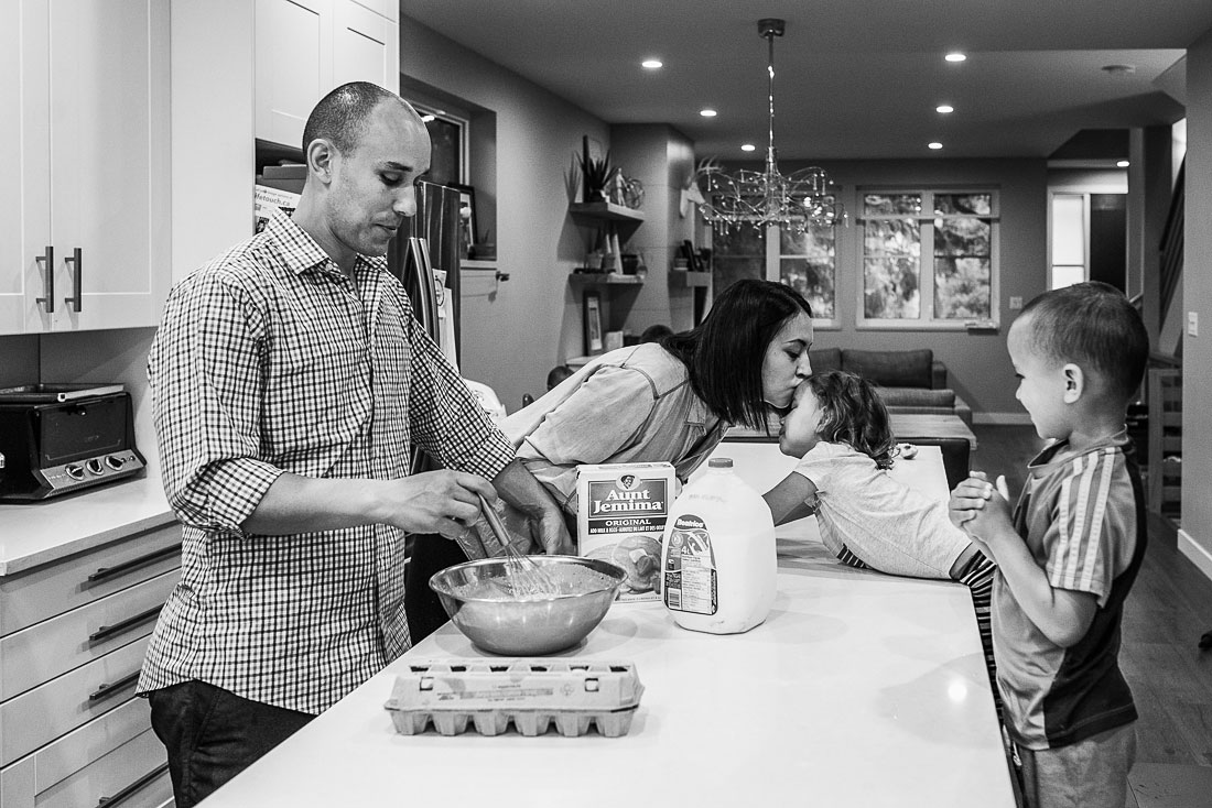 Family making pancakes in the kitchen. Mother kissing daughter on the forehead.