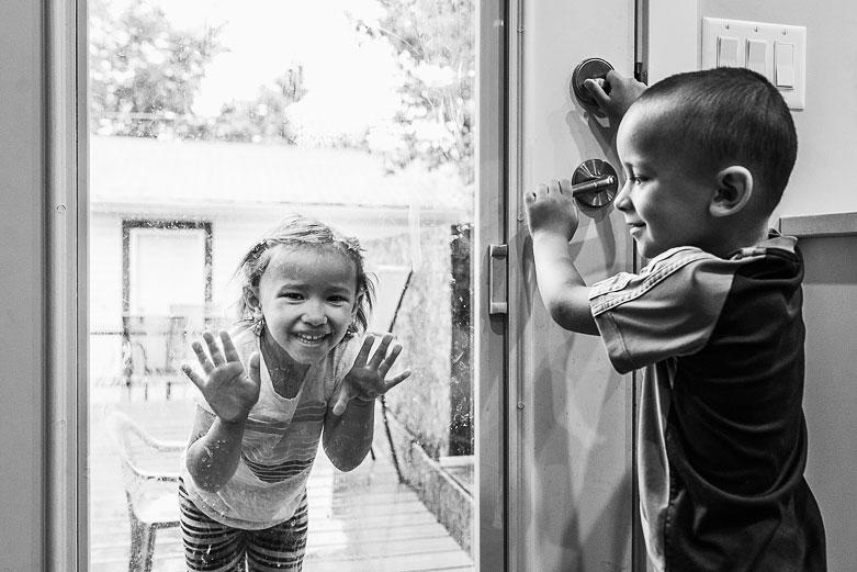 Girl looking through glass door and brother holding door handle