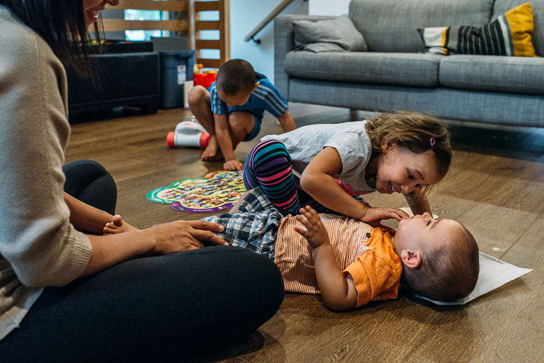 Girl playing with baby brother laying on the floor