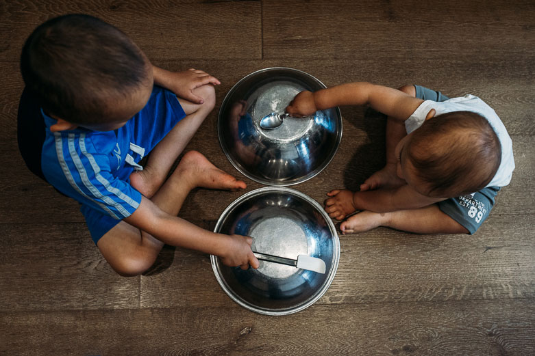 Kids playing with metal kitchen bowls. Seen from above.