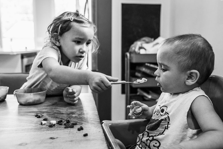 Young girl feeds baby brother
