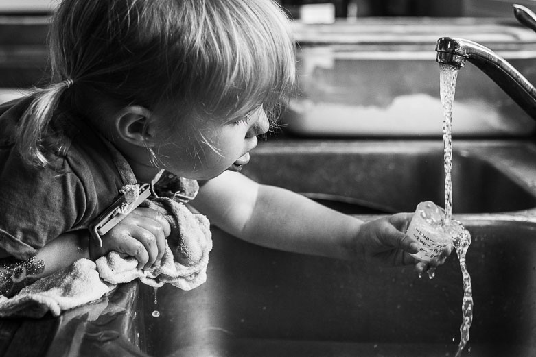 Girl filling small measuring cup with water