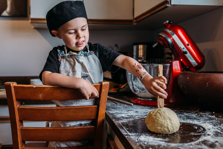 Young boy playing with pasta dough