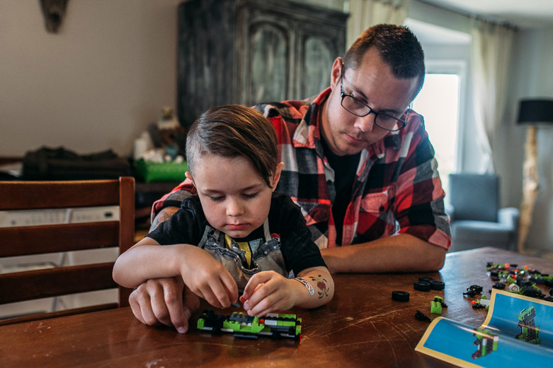 Boy building Lego car with his father