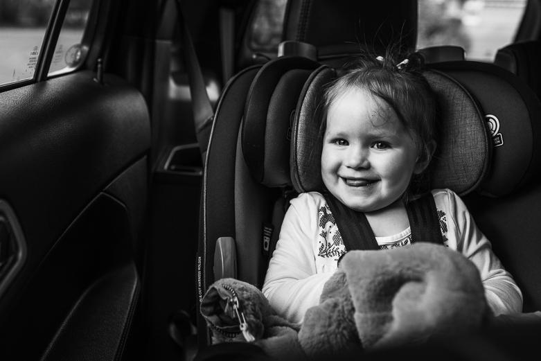 Happy girl in car seat