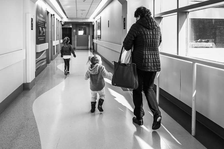 Grandmother and two granddaughters walking down a hospital hallway