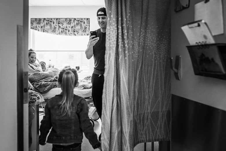 Girl enters hospital room to meet baby brother. Dad takes photos with his phone.