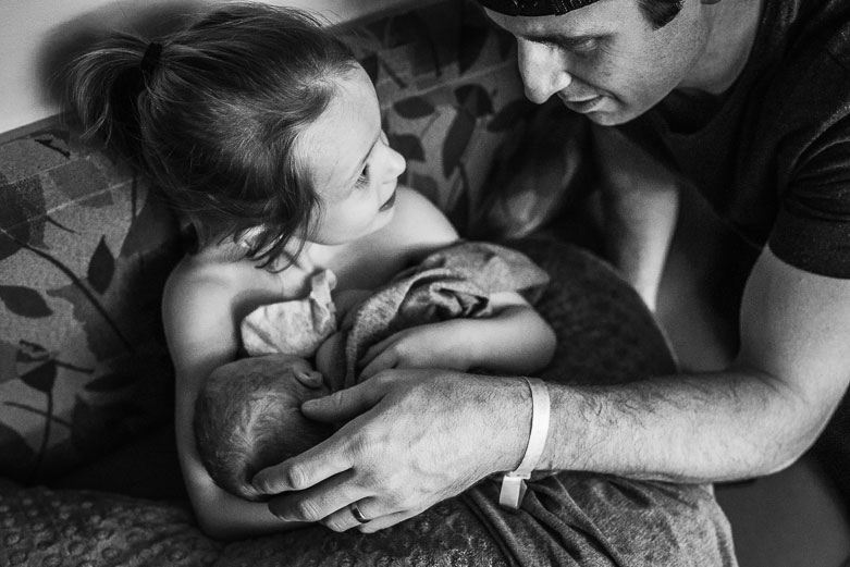 Young girl looking at father as she is doing skin-to-skin with her newborn brother