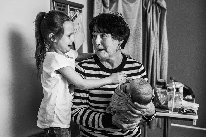 Girl and grandmother giving each other a funny look. Grandmother holding newborn grandson in hospital.