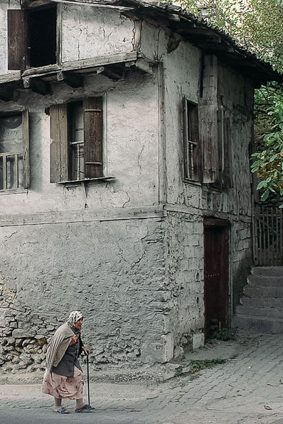 Old woman walking in front of a decrepit building