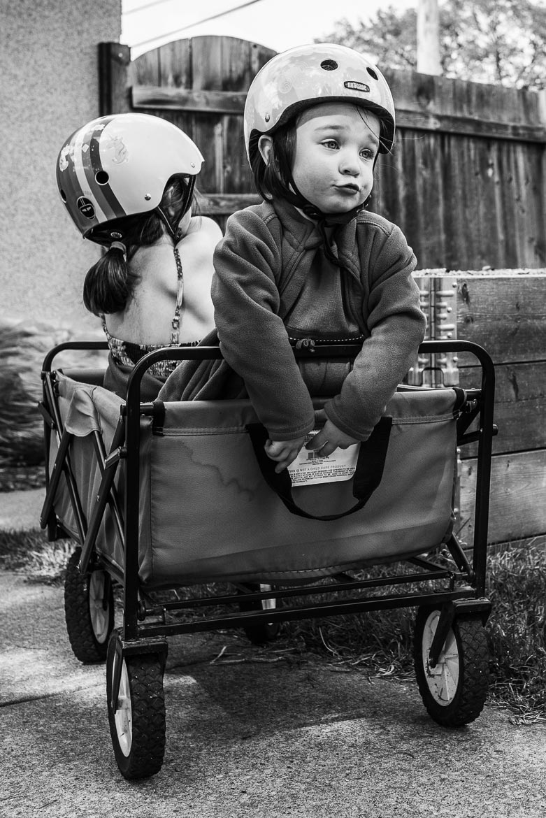 Toddler girl with funny facial expression and helmet on. Sitting in a pull wagon with her sister.