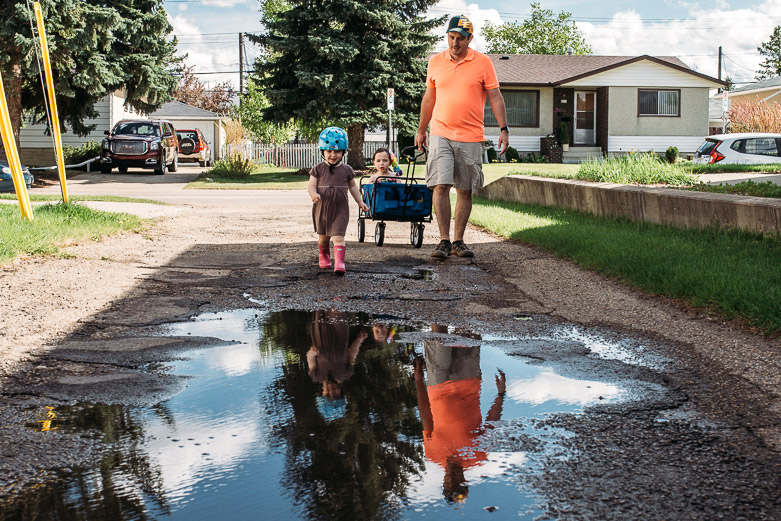 Family arrives by big rainwater puddle