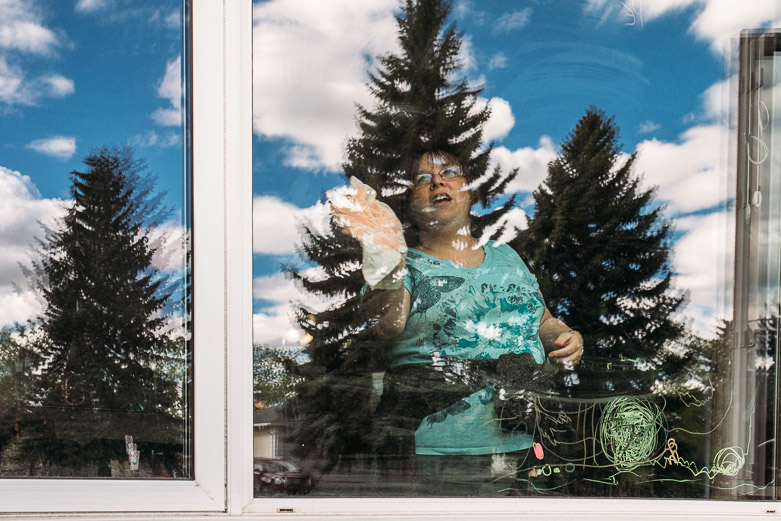 Mother washing drawings off window