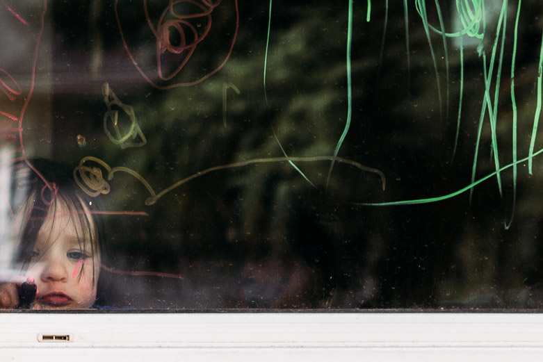 Toddler girl drawing on window