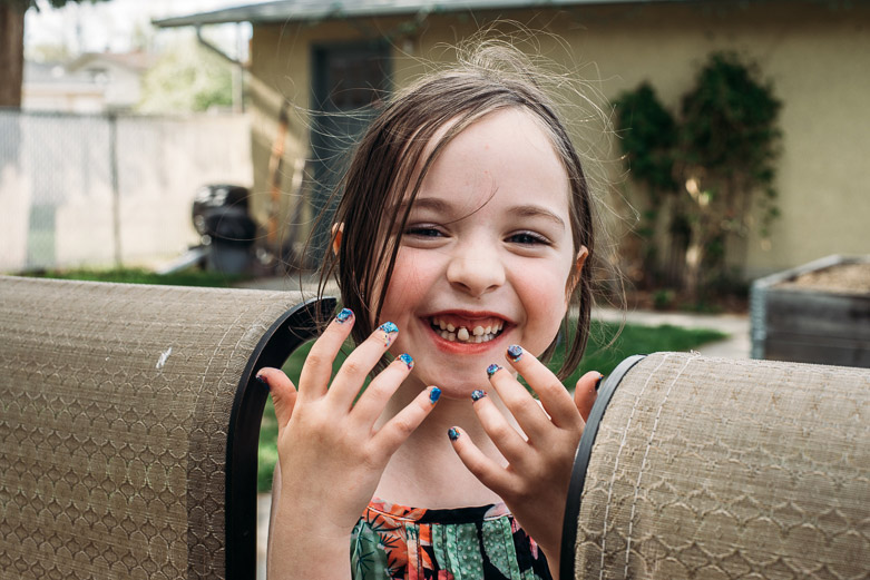 Girl with loose tooth and freshly painted finger nails