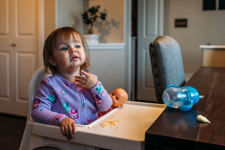 Baby eating cheese in high chair