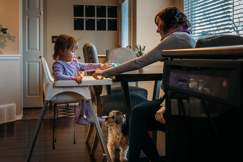 Mother and daughter having breakfast together. Dog waiting for leftover food under the table.