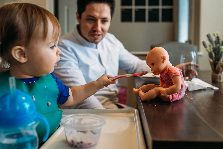 Remember the little things: girl feeding baby doll while dad is observing