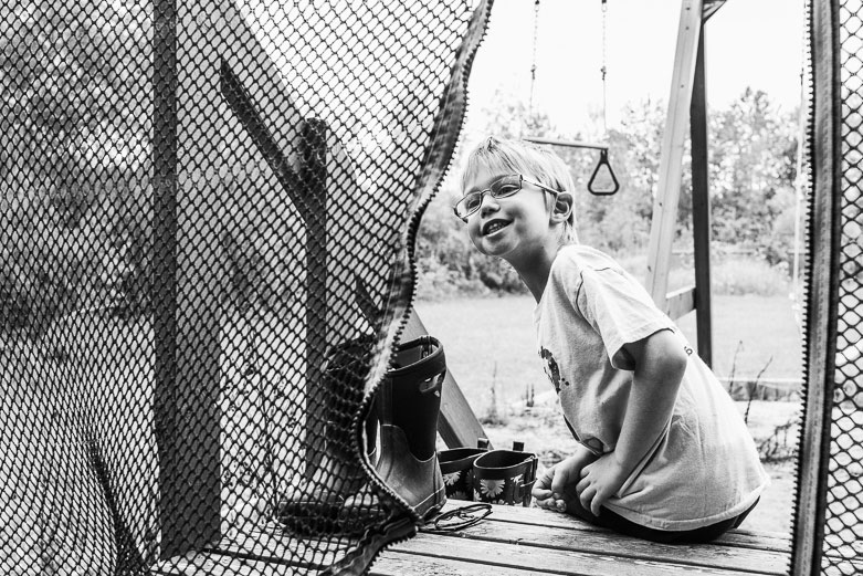 Boy looking through the opening of a trampoline net