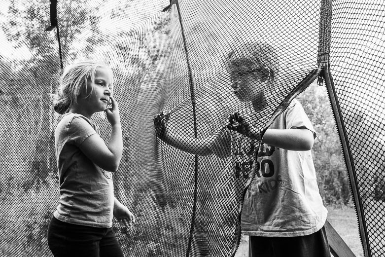 Sister and brother arguing through the safety net of a trampoline