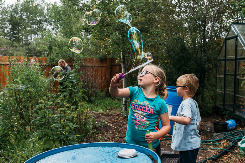 Girl making a trail of bubbles in the garden