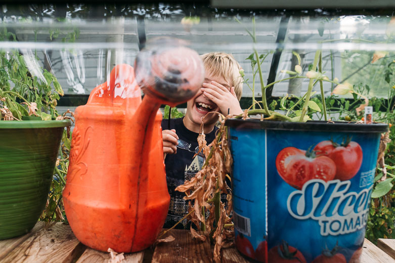 Boy laughing and covering his eyes after spraying water in his glasses while watering a tomato plant