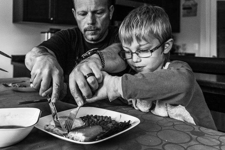 Father helping son cut his food