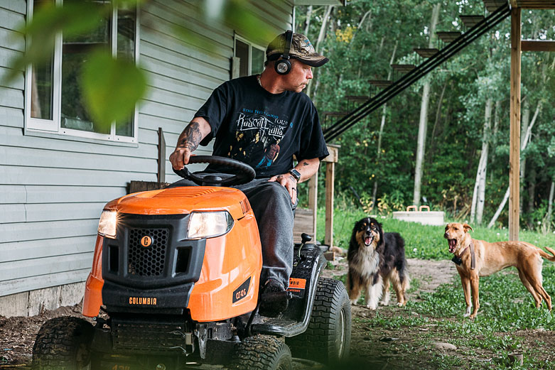 Man on lawnmower looking at his two dogs
