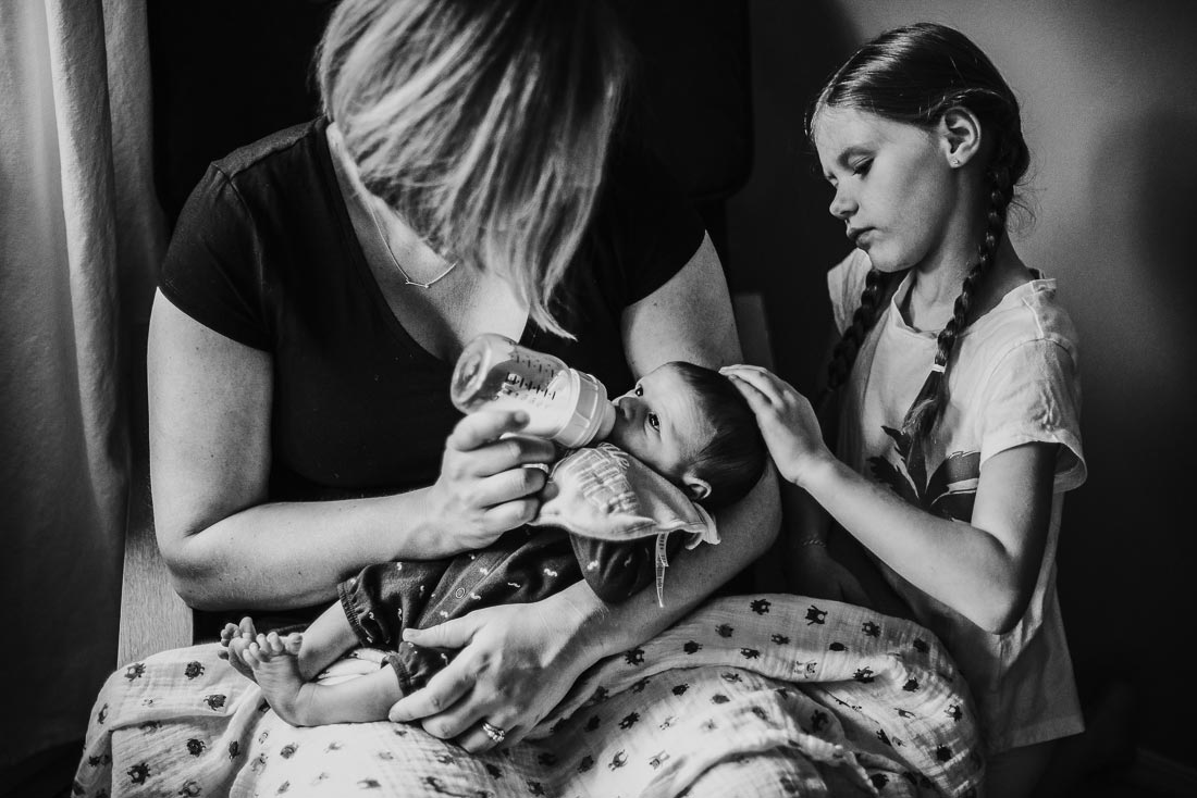 Mother bottle feeding newborn boy. Older sister strokes the baby's hair.