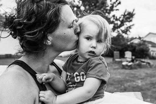 Mother kissing toddler girl