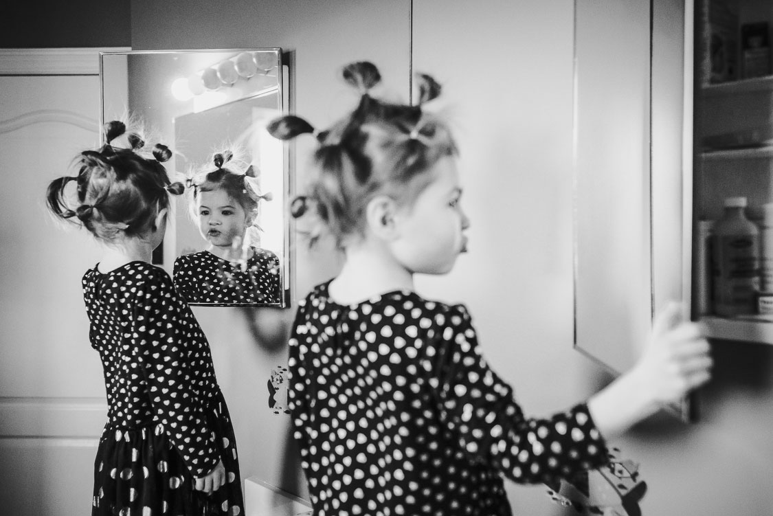 Girl with special hairdo looking at herself in multiple mirrors