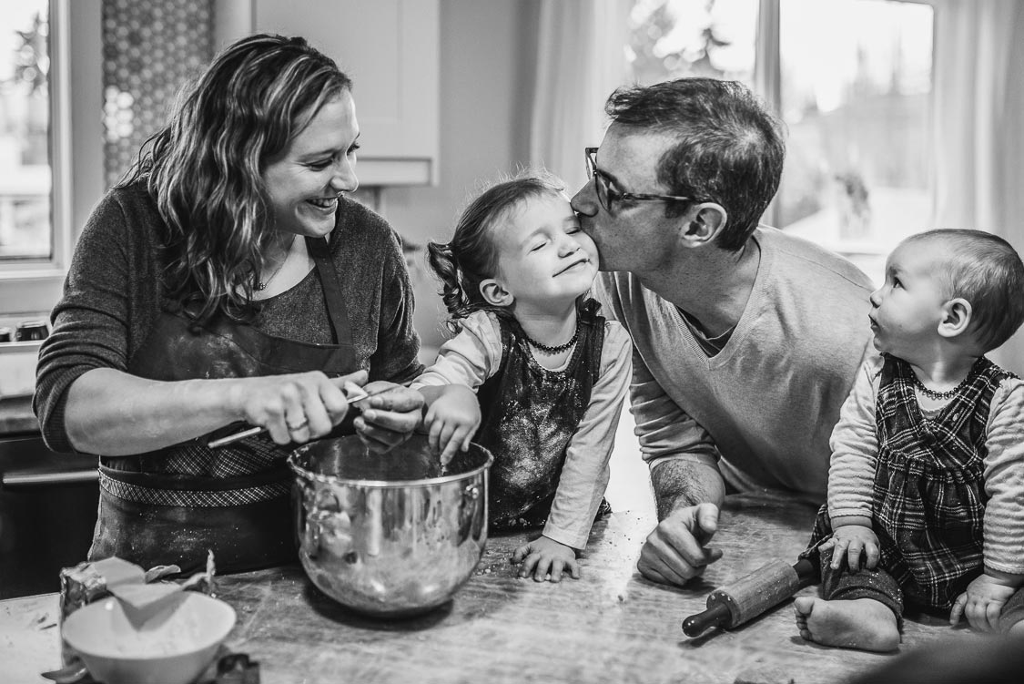 Mom laughing, dad kissing girl, baby looking—It's fun baking Christmas cookies with the kids