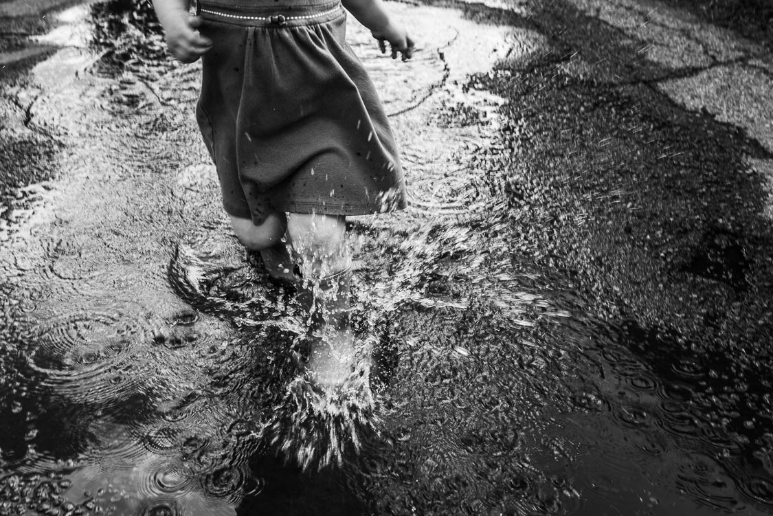 Toddler girl running in rain puddle
