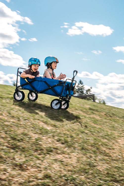 Girls with bike helmets on going down a grassy hill in a wagon