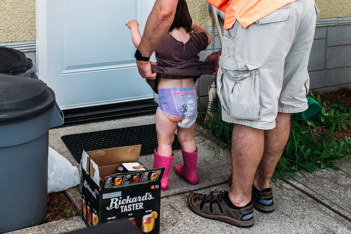 A dad helps take off his toddler girl's wet dress.