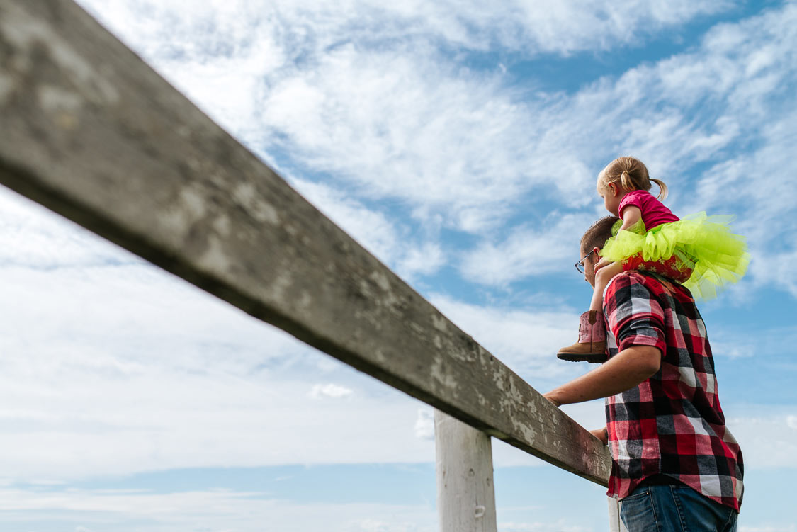 Dad carrying daughter on his shoulder and looking over fence