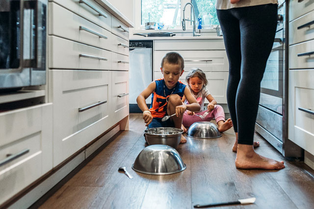 Boy and girl make noise with metal bowls in the kitchen