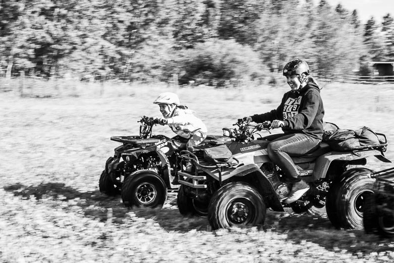 Girl and mom racing on their quads during their outdoor family photo session